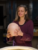 Lori inspects pottery after a bisque firing
