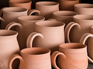 Lori bisque-fired a collection of mugs, varied in size, shape, and design. Next, she will meticulously mask and glaze the mugs in preparation for final glaze firing.